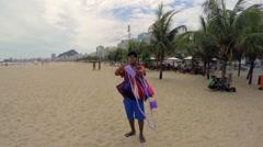 Informal Sales Person Making a Wallet in Copacabana Beach in Rio de Janeiro Stock Footage