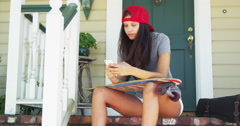 Mixed race woman sitting on porch with skateboard texting Stock Footage