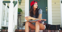 Skatergirl sitting on porch texting Stock Footage