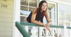 Hispanic woman leaning on rail smiling Stock Footage