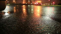 Parking lot windy puddle light reflection during a night time storm Stock Footage