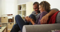 Black couple using smartphone together on couch Stock Footage