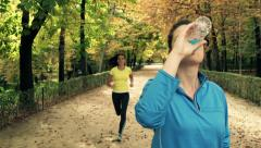 Young, pretty woman drinking water after jogging HD Stock Footage