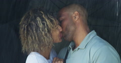 Black couple kissing under umbrella Stock Footage