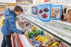 Young boy choosing ice cream at shopping in supermarket Kuvituskuvat