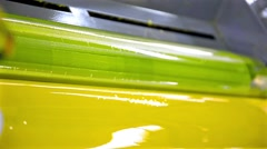 Yellow paint running off a roller in offset printing press, hd loop Stock Footage