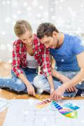 Smiling couple selecting color from samples Stock Photos