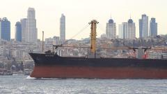 Bulk coal carrier ship with deck cranes sailing past the city Stock Footage