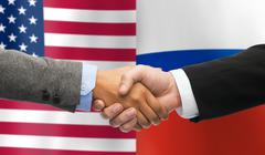 Handshake over american and russian flags Stock Photos