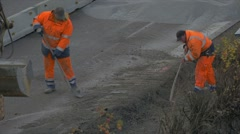 Two construction workers shoveling gravel on highway Stock Footage