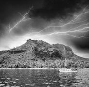 Polynesia. Island and vegetation during a storm with small boat - stock photo