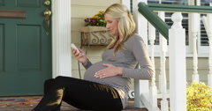 Beautiful pregnant woman sitting on porch using smartphone Stock Footage