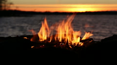 Stock Video Footage of Close view of campfire burning at lakeside during sunset