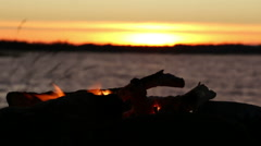Fading campfire at a windy sunset lake - stock footage