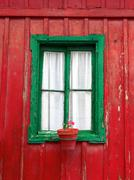 old window on an aged wooden wall of house - stock photo