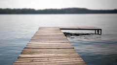 Shot of a wooden dock extending out into the water on a lake Stock Footage