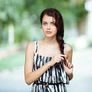 Young beautiful brunette woman with braid hairstyle outdoors portrait - stock photo