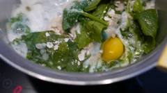 Cooking fresh spinach with egg in a steel pot Stock Footage