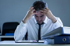 Stressed businessman sitting at desk Stock Photos