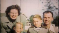 1365 - family of four gather for classic family portrait-vintage film home movie Stock Footage