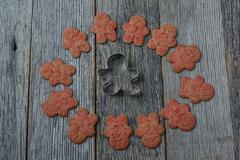 gingerbread cookie and cutter on wood background - stock photo