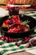 Cranberries and cast iron skillet with chicken Stock Photos