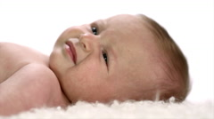 A baby laying on its back starts to cry, close up - stock footage