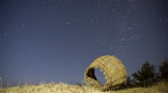 4K Night Time Lapse of stars and illuminated rusty wicker basket Stock Footage