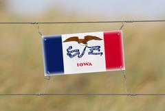Border fence - old plastic sign with a flag Stock Photos