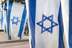 israeli flags held vertically during independence day ceremony - stock photo