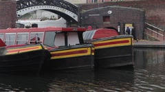 Close Up of Three Narrow Boat Barges Lined in a Row By Bridge - stock footage