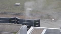 Steam and Smoke Bellows From a Chimney Atop a HighRise Building Stock Footage