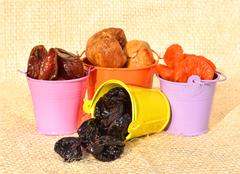 Dried fruit, dates, figs, prunes, apricots on the colored pots Stock Photos