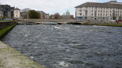 River flowing under busy bridge in Galway, Ireland - stock footage