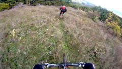 An extreme mountain biker speeds down a  trail during the day. downhill track Stock Footage