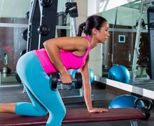 Girl one arm dumbbell bent over row workout Stock Photos
