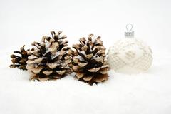 Single decoration of white christmas bauble and pine cones on snow isolated o Stock Photos
