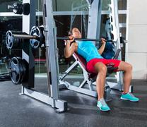 incline barbell bench press woman in multipower - stock photo