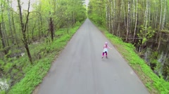 Little girl rides on rollerskates by road along forest Stock Footage