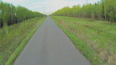 Road with electric power line along forest at spring Stock Footage