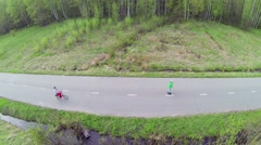 Woman rides on bike with children which ride on rollerskates Stock Footage