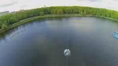 Man rides by pond at spring sunny day in city park. Aerial view Stock Footage