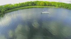 Sportsman turns during ride by Putyaevskii pond at spring day Stock Footage