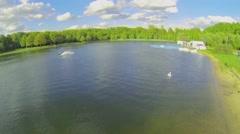 Surfer makes jump stunt during ride by Putyaevskii pond Stock Footage