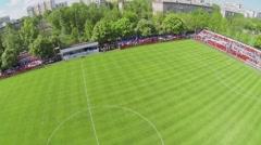 People sit on tribunes around soccer field of Spartakovec stadium Stock Footage