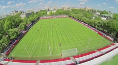 Football match on field with tribunes at spring sunny day Stock Footage