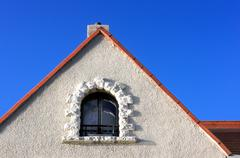 concrete facade with window in a roof attic - stock photo