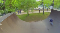 Stock Video Footage of Boy skates on rollerblades by ramp at spring day in park