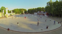 People ride on rollerblades by square near cafe in park Sokolniki Stock Footage