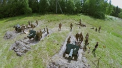 Troops in uniform of Soviet Army of World War II stand near guns - stock footage